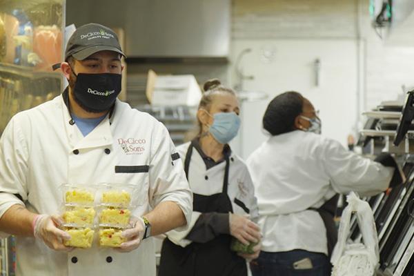 Staff with masks preparing food